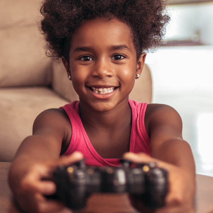 Happy little girl wearing pink shirt holding game controller for digital tool
