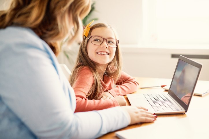 Smiling girl with long hair and yellow bow in hair smiling up at teacher in front of laptop storytelling with digital tool