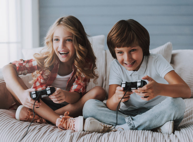 Happy and laughing brother and sister enjoying game together sitting cross legged in couch